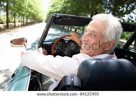 Senior man in sports car - stock photo