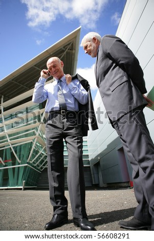 Senior man in suit standing next to a senior man in suit phoning - stock photo