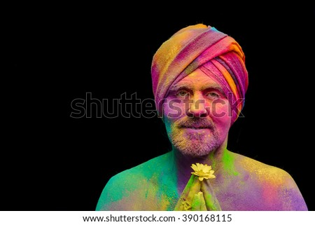 Senior man in traditional Indian turban fully covered with paint holi