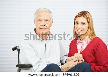 Senior man in wheelchair and daughter holding hands in a nursing home - stock photo