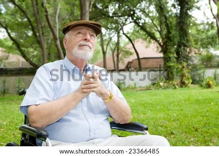 Senior man in wheelchair praying, in a beautiful outdoor setting. - stock photo