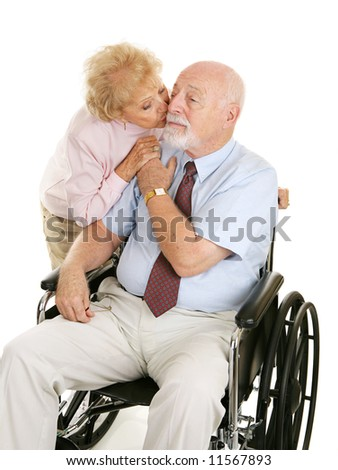 Senior man in wheelchair receiving a kiss from his devoted wife.  Isolated on white. - stock photo