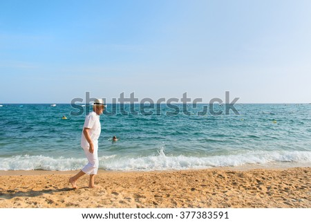 Senior man in white suit walking at the beach  - stock photo