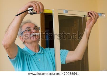 Senior man installing measuring shower box stock photo 490056550 senior man installing and measuring a shower box at home do it yourself solutioingenieria Gallery