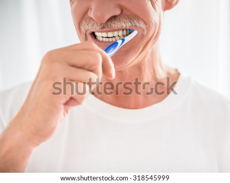 Senior man is cleaning his teeth and smiling. - stock photo