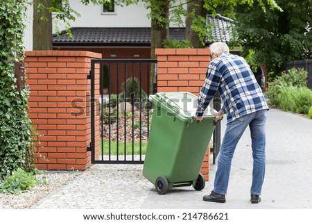 Senior man is pushing wheeled dumpster  - stock photo