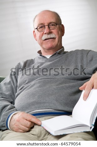 Senior man is reading a book - stock photo