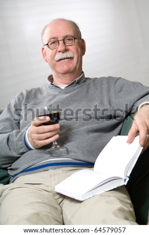 Senior man is reading a book with a glass wine in his hand - stock photo