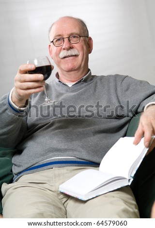 Senior man is reading a book with a glass wine in his hand