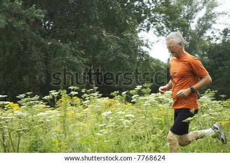 Senior man is running through a field of flowers. - stock photo