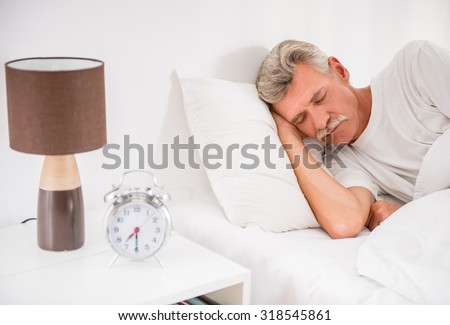Senior man is sleeping in comfortable bed at home.