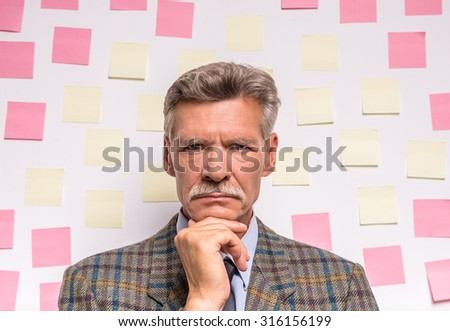 Senior man is standing in front of a board with stickers. - stock photo