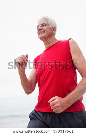 Senior man jogging on the beach on a sunny day
