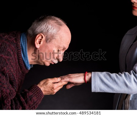 Senior man kissing a woman's hand on a dark background