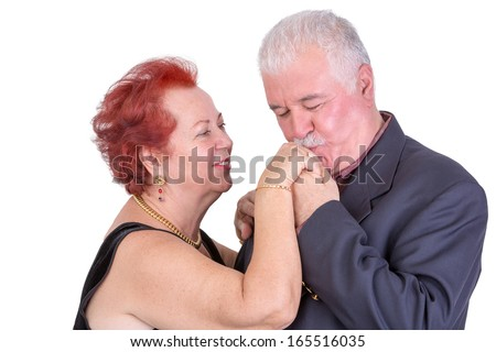 Senior man kissing his wife's hand, both look happy, perhaps its their anniversary - stock photo