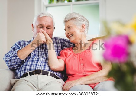 Senior man kissing womans hand in living room - stock photo