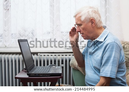 Senior man learning to use a computer at home.