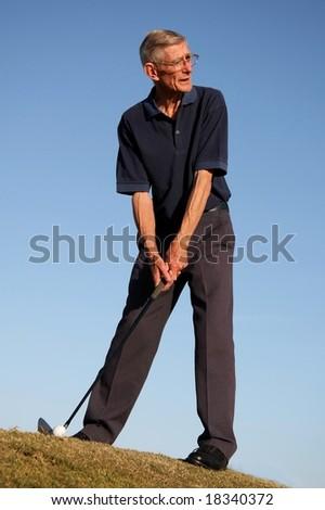 Senior man lining up golf shot in the fairway - stock photo