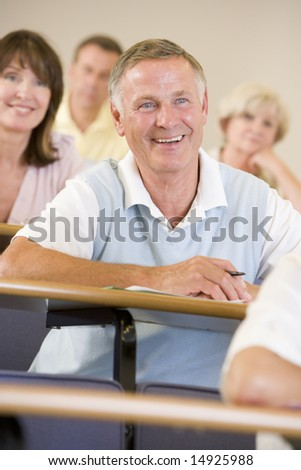 Senior man listening to a university lecture - stock photo