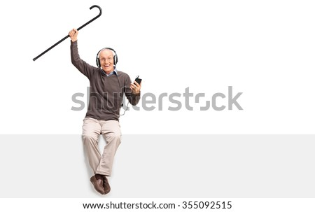 Senior man listening to music on headphones and lifting his cane in the air seated on a blank panel isolated on white background - stock photo