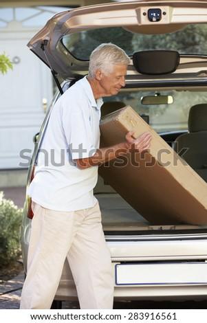 Senior Man Loading Large Package Into Back Of Car - stock photo