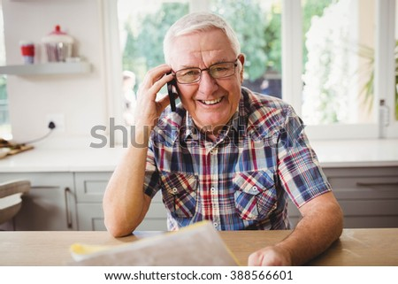 Senior man looking at a document while taking on phone at home - stock photo