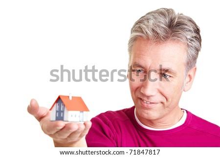Senior man looking at a small miniature house - stock photo