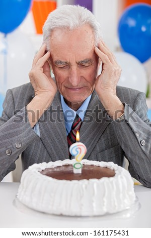 Senior man looking at  birthday cake thoughts about his age - stock photo