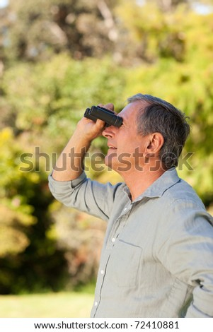 Senior man looking at the sky with his binoculars - stock photo