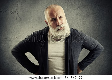senior man looking with distrust at something over dark grey wall