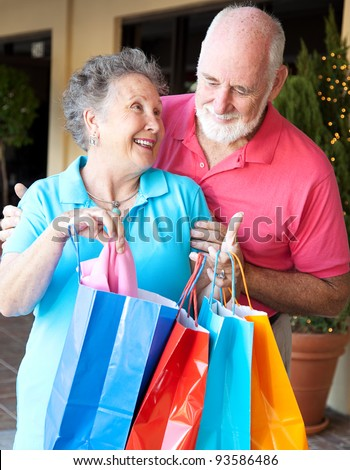 Senior man looks in the shopping bags to see what his wife has bought. - stock photo