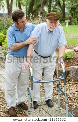 Senior man looks sad as he struggles to walk using a walker.  His adult son is helping him. - stock photo