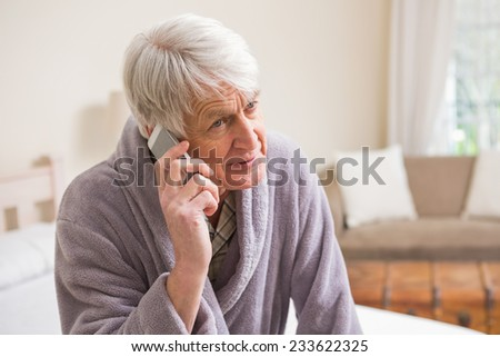 Senior man making a phone call on bed at home in bedroom - stock photo