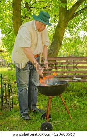 Senior man making BBQ in garden