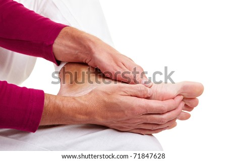 Senior man massaging his aching feet with his hands - stock photo