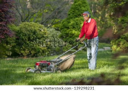 Senior man mowing overgrown lawn in his yard - stock photo