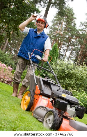 Senior man mowing the lawn. - stock photo