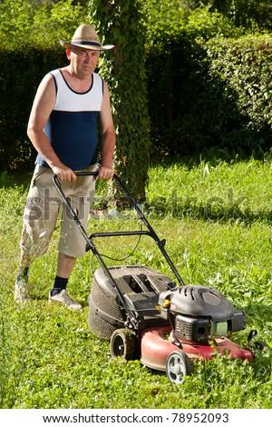 Senior man mowing the lawn - stock photo