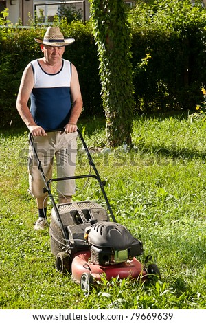 Senior man mowing the lawn - stock photo