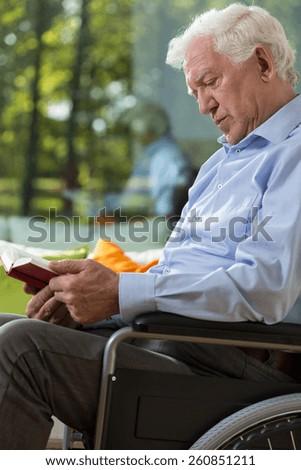 Senior man o wheelchiar is reading a book - stock photo