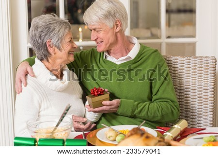 Senior man offering a christmas present to his wife at home in the living room