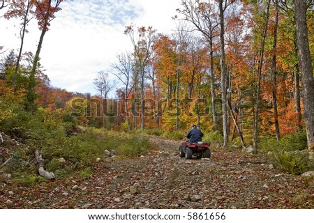 Senior man on a four wheel ATV in a dirt road, surrounding by an colorful autumnal fairy decor, Quebec, Canada
