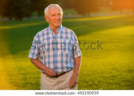 Senior man on grass background. Male is holding a ring. Waiting for beloved one. There's always hope.