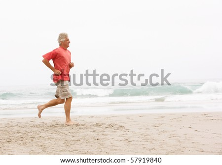 Senior Man On Holiday Running Along Winter Beach