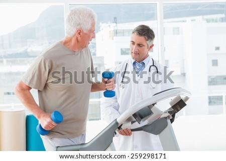 Senior man on treadmill with therapist in fitness studio - stock photo