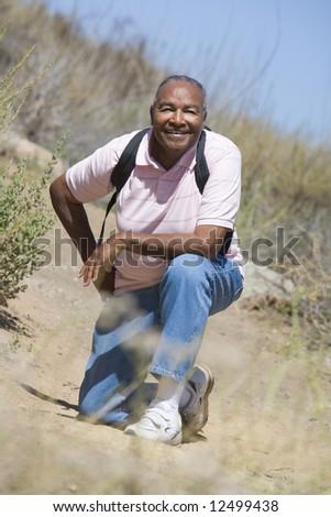 Senior man on walk in countryside - stock photo