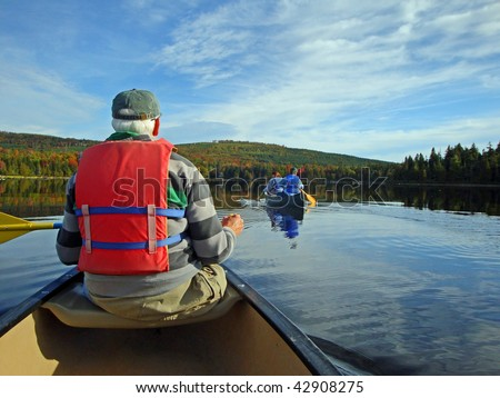Senior man paddling a canoe with second canoe, calm waters and autumn colors in background. - stock photo