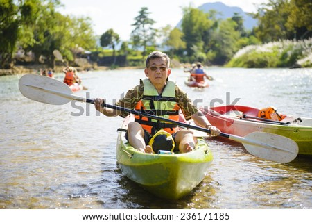 Senior man paddling kayak - stock photo