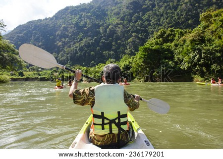 Senior man paddling kayak at river - stock photo