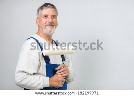 Senior man painting a wall in his home, smiling, enjoying the work - stock photo